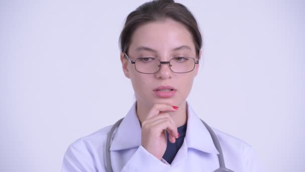 Face of serious young woman doctor thinking and looking down