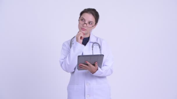 Happy young beautiful woman doctor thinking while using digital tablet