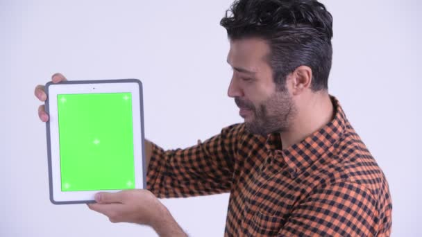 Face of happy bearded Persian hipster man showing digital tablet