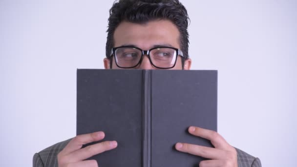 Face of Persian businessman covering face with book