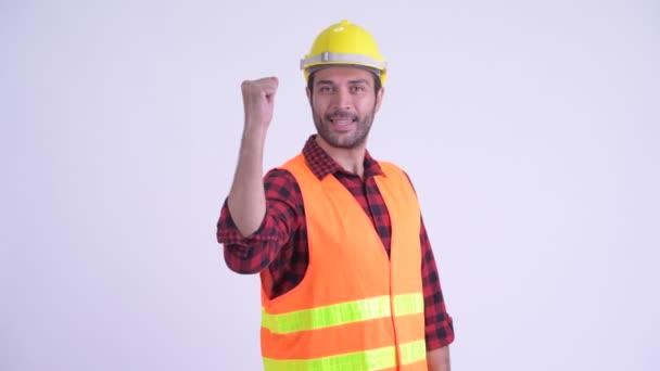 glücklicher bärtiger persischer Bauarbeiter mit erhobener Faust