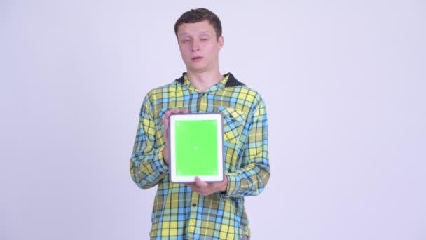 glücklicher junger gutaussehender Mann zeigt digitales Tablet und wirkt überrascht