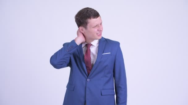 Stressed young businessman having neck pain
