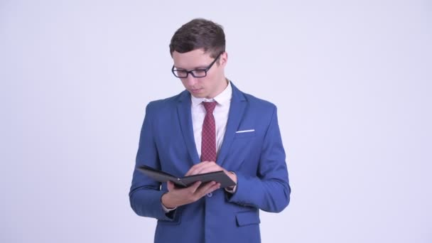 Young handsome businessman reading book with eyeglasses