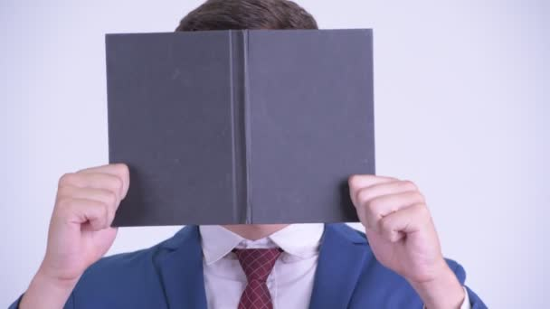 Face of young businessman hiding behind book