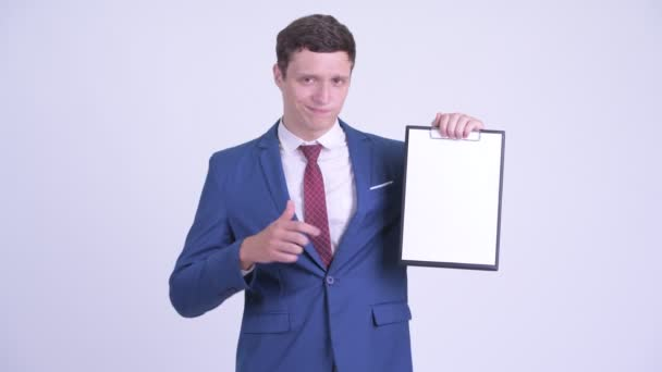 Serious young businessman holding clipboard and giving thumbs down