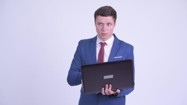 Happy young handsome businessman thinking while using laptop