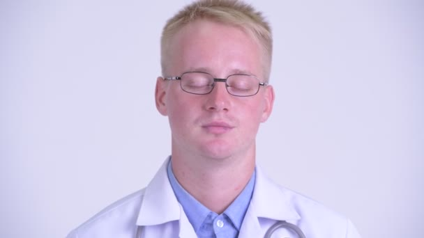 Face of serious young blonde man doctor nodding head no