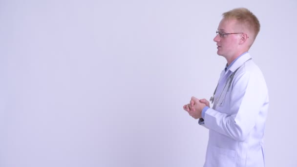 Profile view of young blonde man doctor talking and explaining