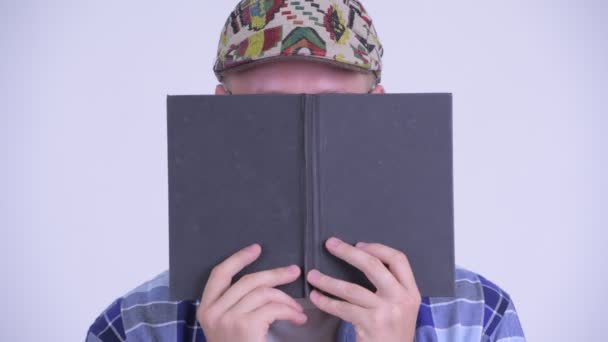 Face of young hipster man thinking while covering face with book