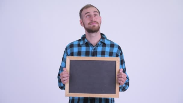 Happy bearded hipster man thinking while holding blackboard