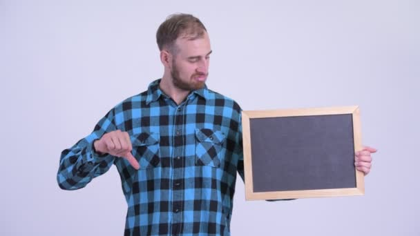 Stressed bearded hipster man holding blackboard and giving thumbs down