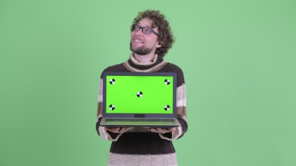 Happy young bearded man thinking while showing laptop