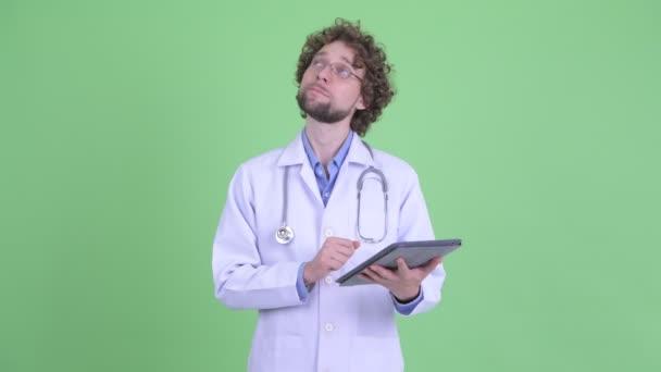 Šťastný mladý vousatý doktor, který si myslí, že používá digitální tablet