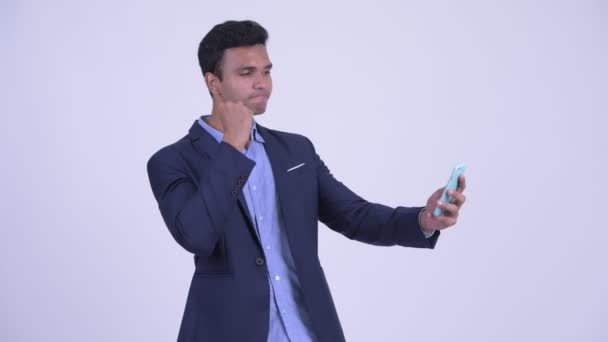 Happy young Indian businessman using phone and looking surprised