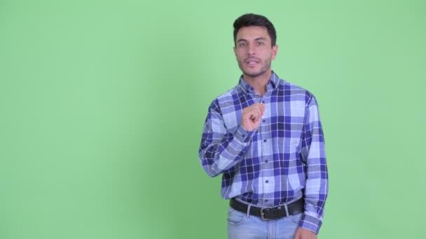 Young handsome Hispanic man touching and explaining something
