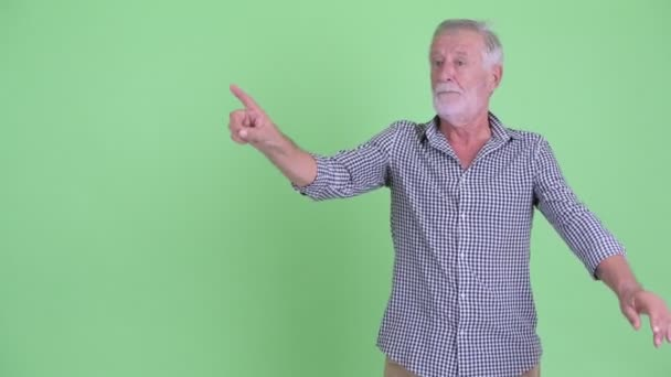 Senior bearded man touching something and giving thumbs down
