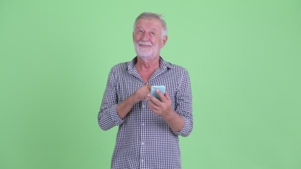 Happy senior bearded man thinking while using phone