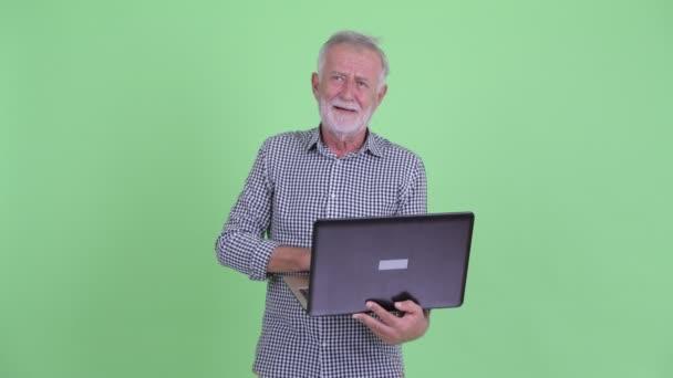 Happy senior bearded man thinking while using laptop