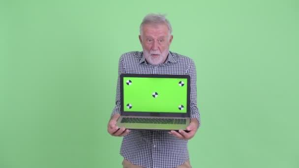 Glücklicher Senior bärtigen Mann zeigt Laptop und sieht überrascht