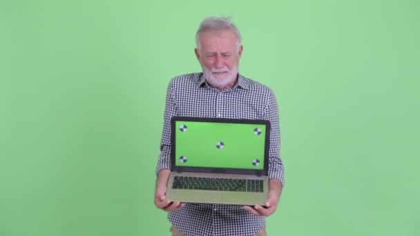 Gestresste Senior bärtigen Mann zeigt Laptop und immer schlechte Nachrichten