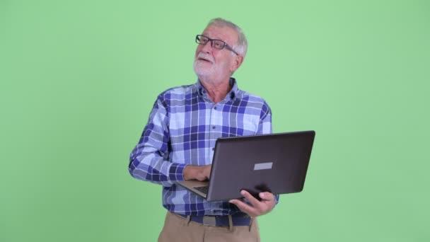 glücklich Senior bärtigen Hipster-Mann denken, während mit Laptop