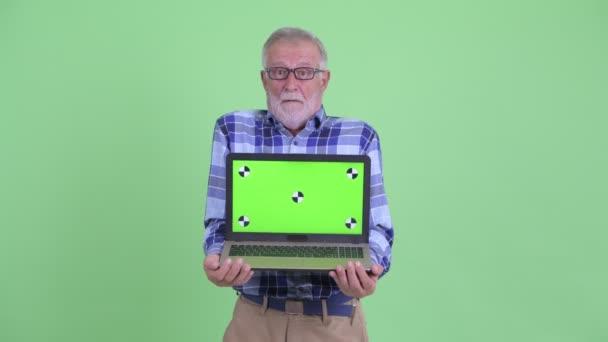 Glücklich Senior bärtigen Hipster Mann zeigt Laptop und sieht überrascht