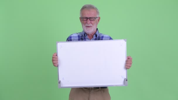 Stressed senior bearded hipster man holding white board and getting bad news