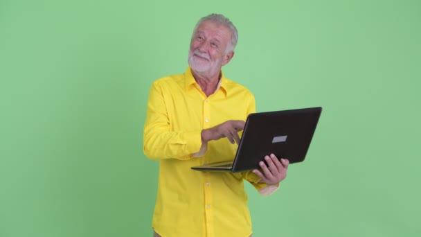 Glücklicher Senior bärtigen Geschäftsmann denken, während mit Laptop