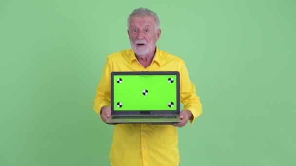 Glücklicher Senior bärtigen Geschäftsmann zeigt Laptop und sieht überrascht
