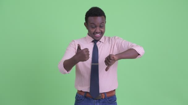 Confused young African businessman choosing between thumbs up and thumbs down