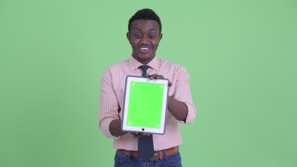 Happy young African businessman showing digital tablet and looking surprised