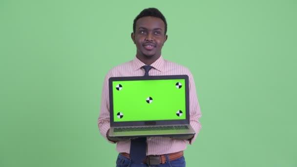 Šťastný mladý africký obchodník při zobrazování přenosného počítače