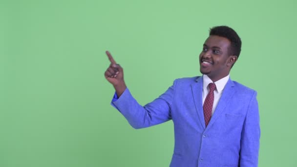 Happy young African businessman pointing up