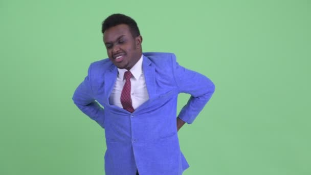 Stressed young African businessman having back pain