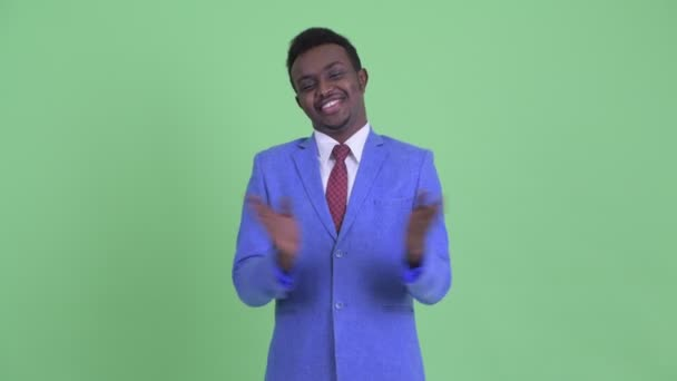 Happy young African businessman clapping hands