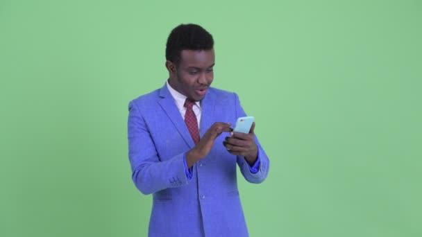 Boldog fiatal afrikai üzletember a telefon segítségével, és egyre jó hír