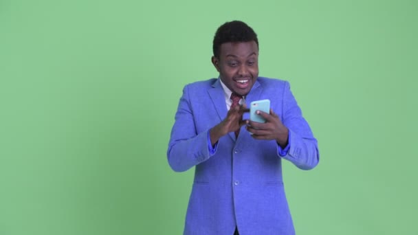 Happy young African businessman using phone and looking surprised