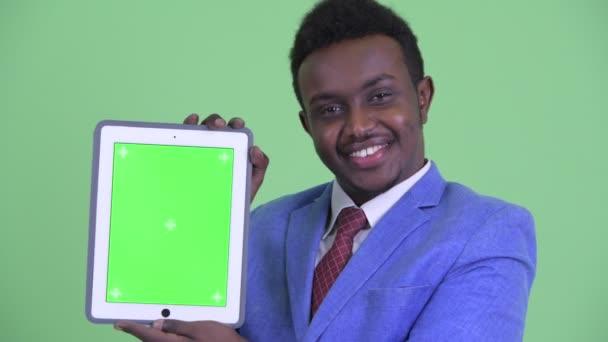 Tvář šťastného mladého afrického podnikatele zobrazující digitální tablet