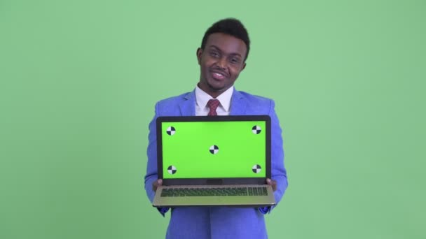 Happy young African businessman talking while showing laptop