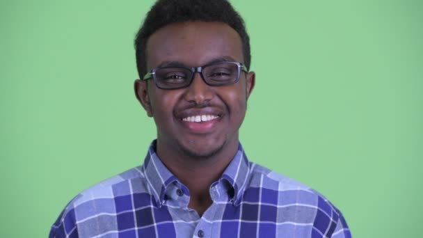 Face of happy young African hipster man with eyeglasses smiling and laughing