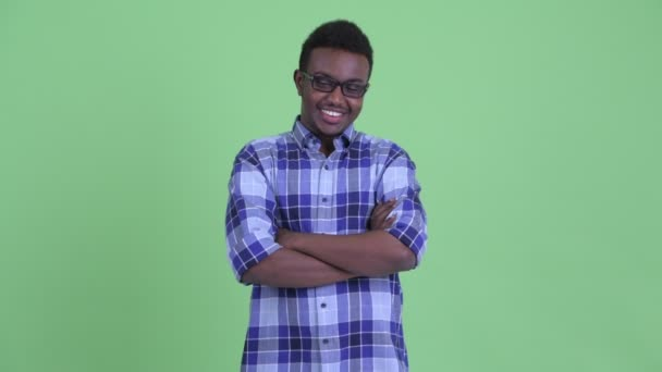 Happy young African hipster man smiling with arms crossed