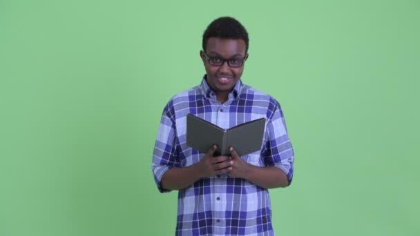 Boldog fiatal afrikai csípő ember olvasási könyvet, és integetett kézzel