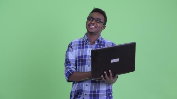 Boldog fiatal afrikai csípő ember gondolkodás használata közben laptop