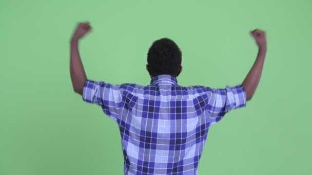 Rear view of happy young African hipster man with fists raised