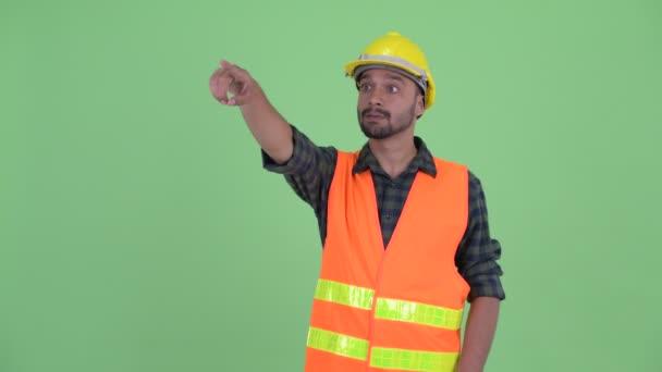 Šťastný mladý vousatý Peršan muž ukazující prstem