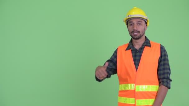 Šťastný mladý vousatý Peršan chlap, který chytne prsty a dává palce