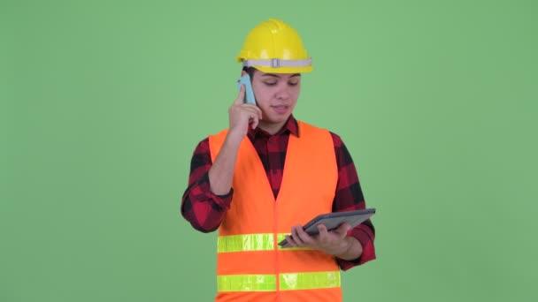 Šťastný mladý stavební pracovník, který při používání digitálního tabletu mluví na telefonu