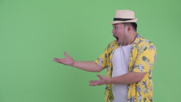 Boldog fiatal túlsúlyos ázsiai turista férfi mutat valamit, és keresi meglepett