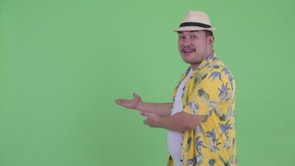 Happy young overweight Asian tourist man talking while showing to back